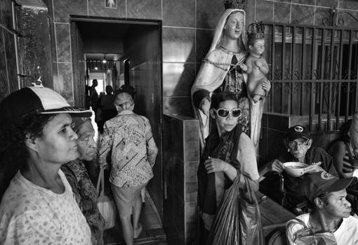 Beneficiarios del comedor social Casa de María esperan su turno para poder disfrutar de su almuerzo