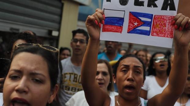 Una mujer en Caracas sostiene una pancarta donde pide que Rusia, Cuba y China se alejen del país