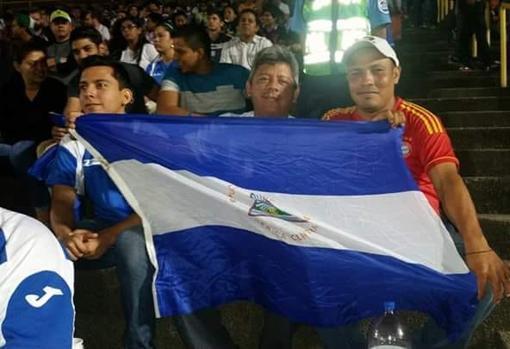 De izquierda a derecha, Kevin y su padre Roberto, junto a un amigo, durante un partido de fútbol con la bandera de Nicaragua