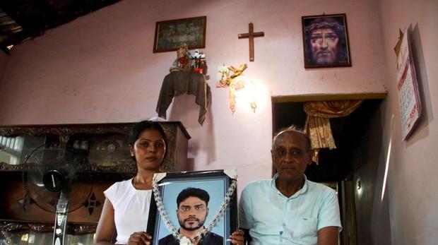Patrick Fernando sostiene el retrato de su hijo, Marians Niranjan, junto a su viuda, Rupaseeli Kumari, que se salvó de milagro del atentado en la iglesia de San Sebastián en Negombo