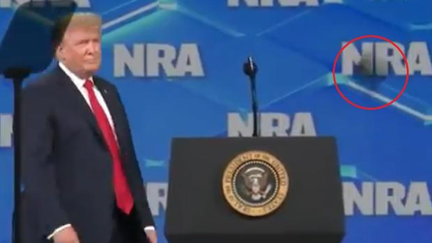 Momento en el que lanzan un móvil cerca de Trump