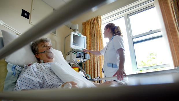 Una enfermera chequea el nivel de oxígeno de una paciente en un hospital del Servicio de Salud británico, en Sheffield
