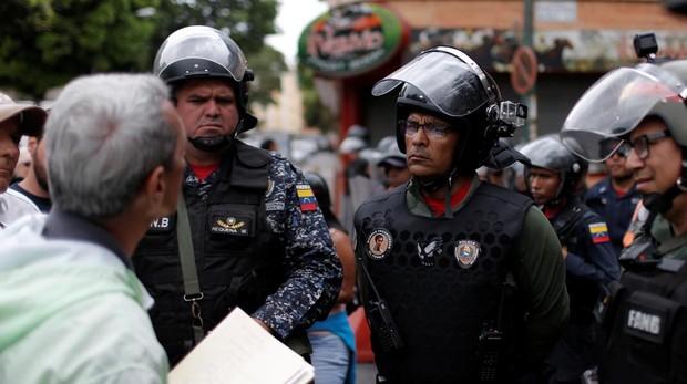 Una manifestante lee la proclama a un grupo de agente de la PNB