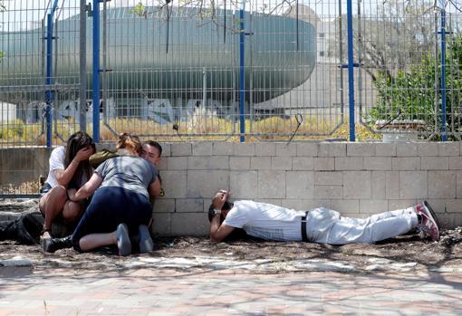 Ciudadanos israelíes aterrorizados durante un ataque de cohetes de Hamás hoy, en Ashkelon