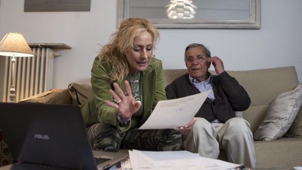 Elena Cáceres y su padre, Francisco, revisan documentos sobre los bienes confiscados a un pariente
