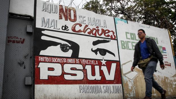 Un hombre pasa frente a un mural chavista en un barrio de Caracas
