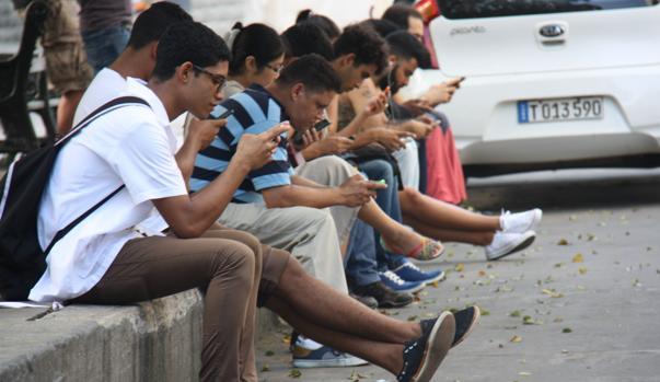 Cubanos consultan sus teléfonos móviles en un punto con internet en La Habana