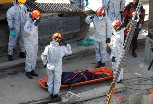 Miembros de los servicios de rescate ante el cuerpo de una de las víctimas mortales del barco naufragado en el río