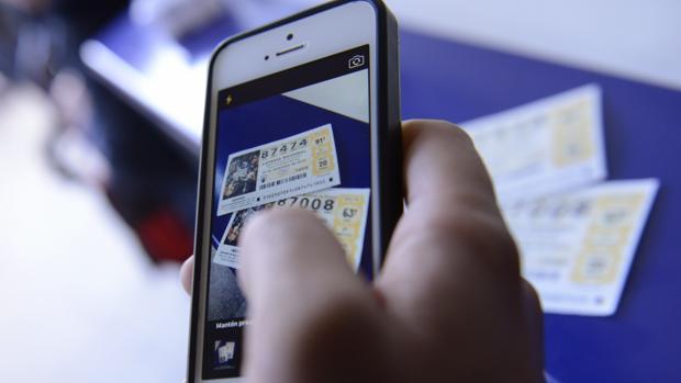 Un joven le hace una foto a sus décimos de Lotería de Navidad