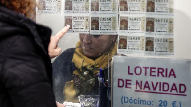 Una mujer escoge un décimo en la Administración número 11 en Valencia