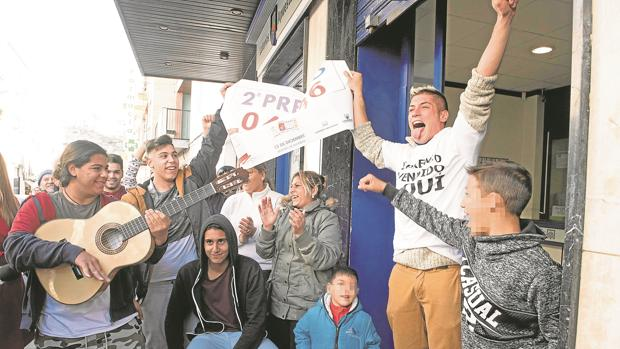 Varias personas festejan el segundo premio, frente a una administración de Granada