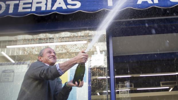 Sergio Martín, propietario de una administración de lotería de la calle Orense, celebra un cuarto premio de la lotería de Navidad en 2015