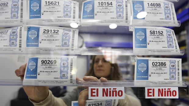 Una lotera coloca décimos de la Lotería del Niño en su administración