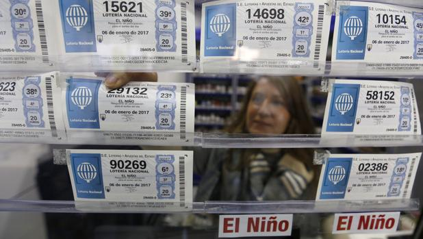Una lotera coloca boletos de la Lotería del Niño en su administración en Córodoba