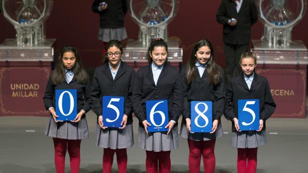 Los niños de San Ildefonso muestran el número agraciado con el primer premio de la Lotería del Niño, que ha recído en el 05.685.