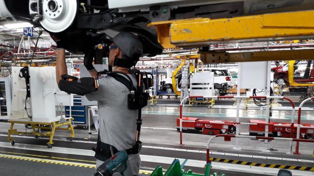Operario con exoesqueleto en la factoría de PSA de Vigo