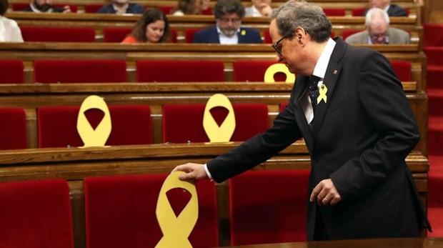El presidente de la Generalitat, Quim Torra, coloca un lazo amarillo en el Parlament
