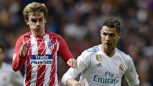 El futbolista del Atlético de Madrid Antoine Griezmann corre ante la mirada de Cristiano Ronaldo
