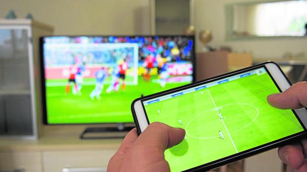 Un usuario sintoniza un partido de fútbol en la televisión mientras ve un vídeo en su teléfono móvil