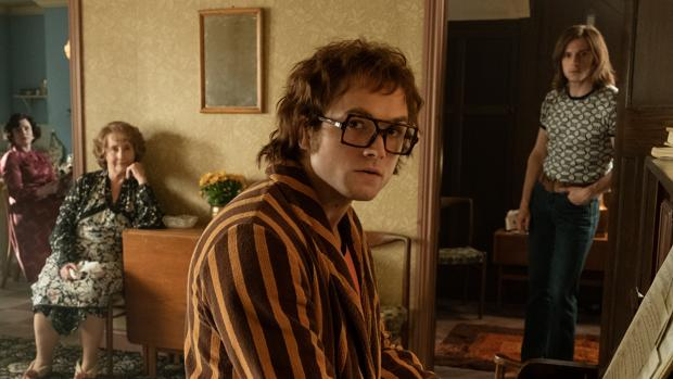Elton John (Taron Egerton), interpreta una canción al piano, en su casa, antes de ser la estrella mundial del pop