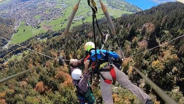 El youtuber se agarra al piloto y a una barra del ala delta para no caer al vacío
