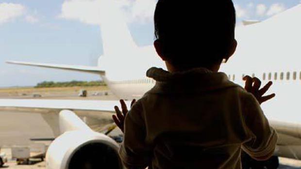 Un niño pequeño mirando un avión