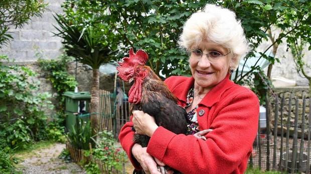 Corinne Fesseau posa con su gallo Mauriice en el jardín de su casa
