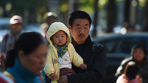 Uh hombre lleva a su hijo en brazos cerca de un hospital de Beijing, el 30 de octubre de este año