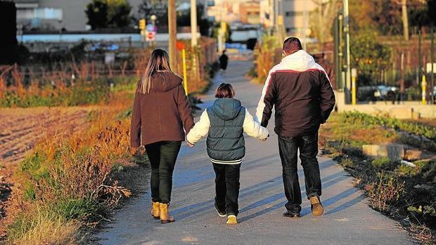 Un niño aquejado por una enfermedad rara camina con sus padres por Sant Joan Despi (Barcelona)