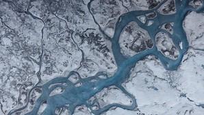 Esta vista aérea de Groenlandia muestra ríos de agua de deshielo y áreas de hielo oscuro