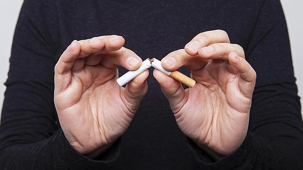Un ex fumador hace un gesto de no al tabaco, rompiendo unos cigarrillos