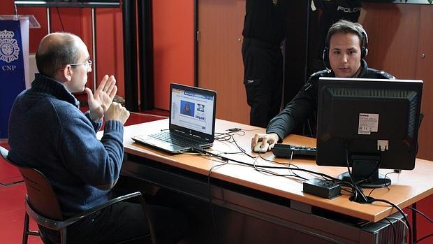 Una persona con discapacidad auditiva se comunica con el agente de la Policía Nacional