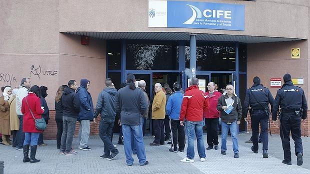 Varias personas esperan a las puertas de una oficiina de empleo