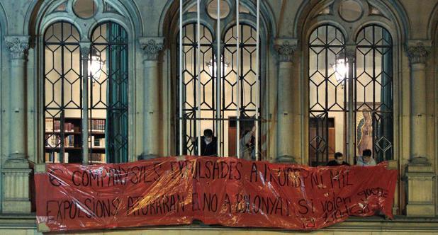 Varios estudiantes colocan una pancarta en los balcones del Rectorado de la Universidad de Barcelona con el lema «6 companys/es espulsades a la UAB. Ni mil expulsions aturaran el NO a Bolonia. Si volen guerra la tindrán (6 compañeros expulsados en la Universidad Autonoma de Barcelona». La imagen es de diciembre de 2008