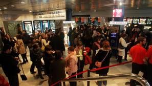 Varios espectadores a la entrada de un cine en Madrid