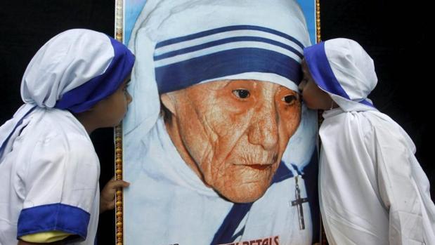 Dos niñas vestidas como Misionerasde la Caridad besna un retrato de la Madre Teresa de Calcuta