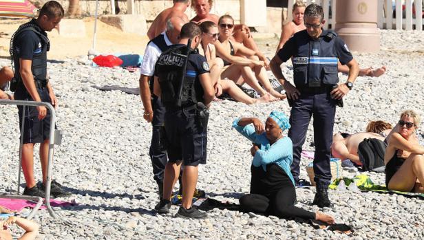 Los policías se acercan a la mujer con «hijab»