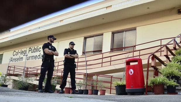 Dos policías locales permanecen a la entrada del colegio público Anselm Turmeda del barrio obrero de Son Roca de la capital balear