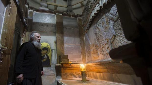 Un clero griego ortodoxo junto a la tumba de Jesucristo en la Iglesia de la Santa Sepultura en Jerusalén