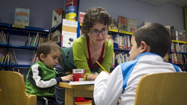 Paloma, en la biblicoteca haciendo deberes con sus dos hijos