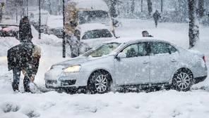 Un hombre limpia la calle de nieve para tratar de sacar su coche durante una nevada en Estocolmo