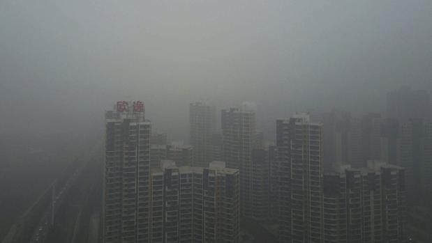 El esmog, una mezcla de niebla y partículas contaminantes, cubre los edificios en el distrito de Yanjiao en Sanhe (China)