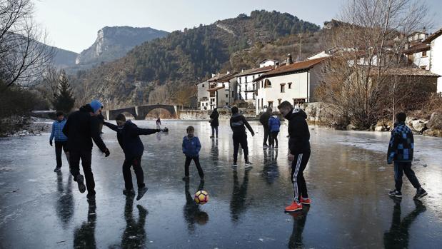 Un grupo de jóvenes juegan al balón sobre la superficie helada del Río Esca a su paso por la localidad navarra de Burgui