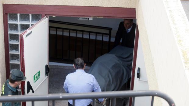 Operarios de la funeraria se llevan el cadáver de una mujer en una residencia de El Campello (Alicante), probablemente la última víctima de violencia de género