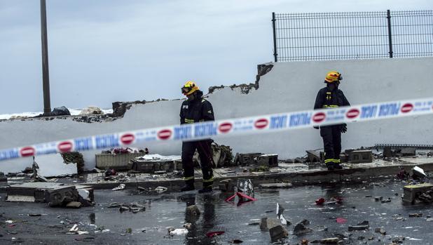 Unos bomberos supervisan el muro caido del paseo marítimo de la playa De Sacaba por el mal temporal, hoy en Málaga