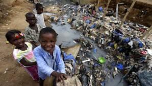 Varios niños juegan junto a un río contaminado en una barriada de chabolas en Azito, Abiyán (Costa de Marfil), antes de celebrar, hoy, el Día Mundial contra la Malaria