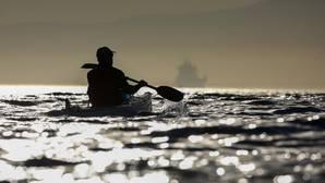 Un hombre rema en un kayak en el Océano Atlántico en la costa de Ciudad del Cabo