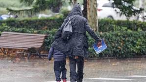 Una madre protege a su hijo de la lluvia y las bajas temperaturas
