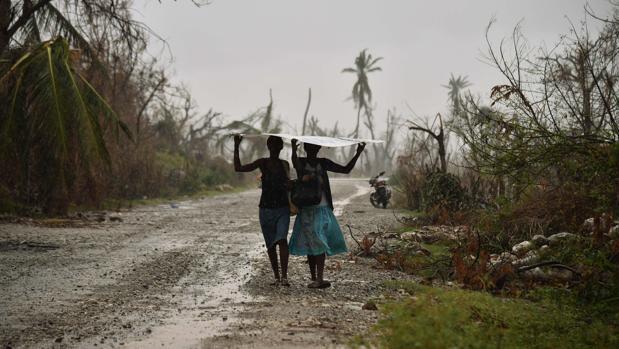 Imagen de archivo de dos mujeres protegiéndose de la lluvia en Haití, en 2016