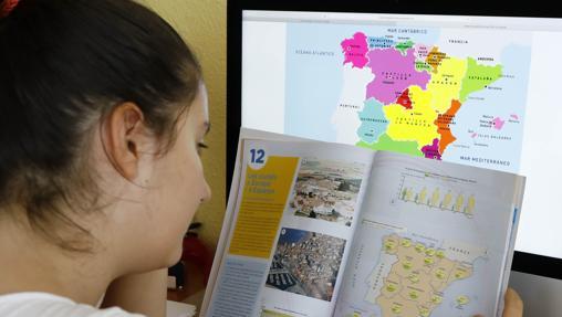 Una alumna de 2º de la ESO estudia el mapa de España en el libro de texto de Geografía e Historia, en su domicilio de Alicante
